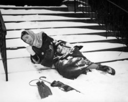 1950s woman lying on snow covered steps fall accident slip expression of pain